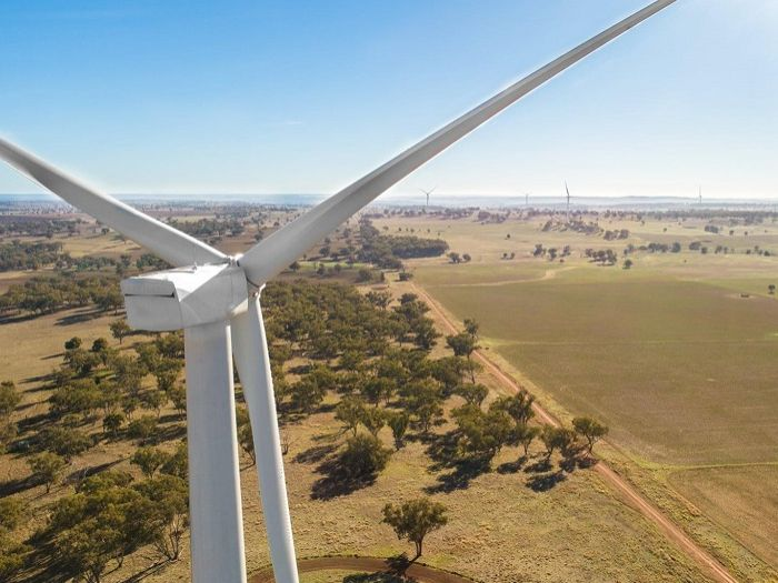 An image from the air shot from behind a wind turbine, looking over paddocks and a number of other turbines.