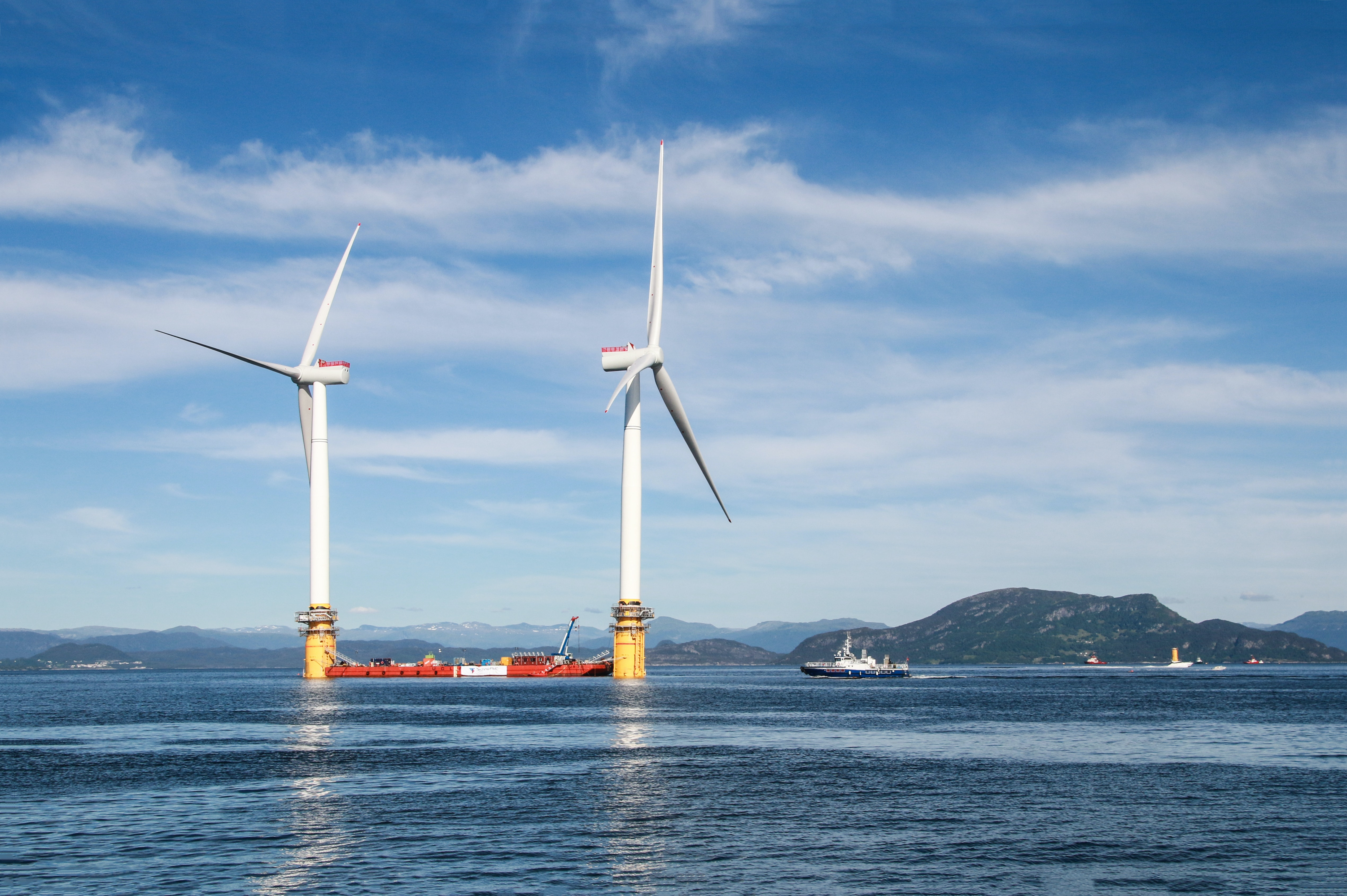 Two floating wind turbines with a ship in between.