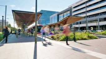Canberrans walk around the light rail station in Civic.