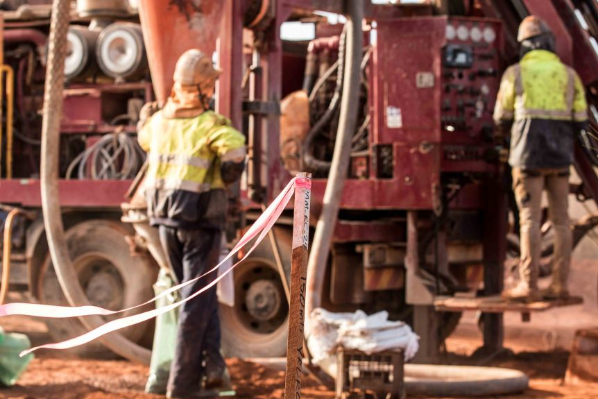 Two men wearing high-vis workwear working on a drill rig in bushland.