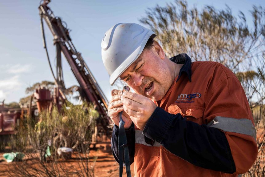 A geologist wearing high-vis workwear inspects drilling samples in the bush.