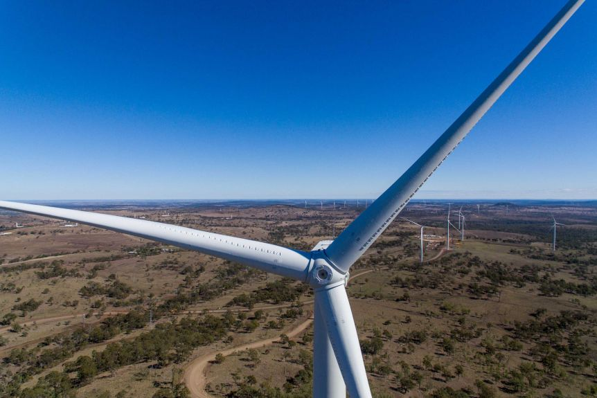 A drone shot of a large wind turbine with dozens of other turbines in the background.