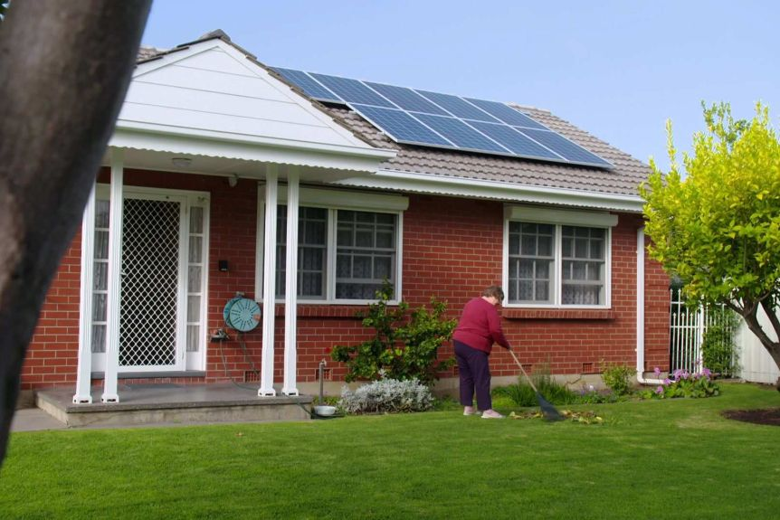 Marianne Hun rakes leaves in front of her red-brick house with solar panels on the roof.