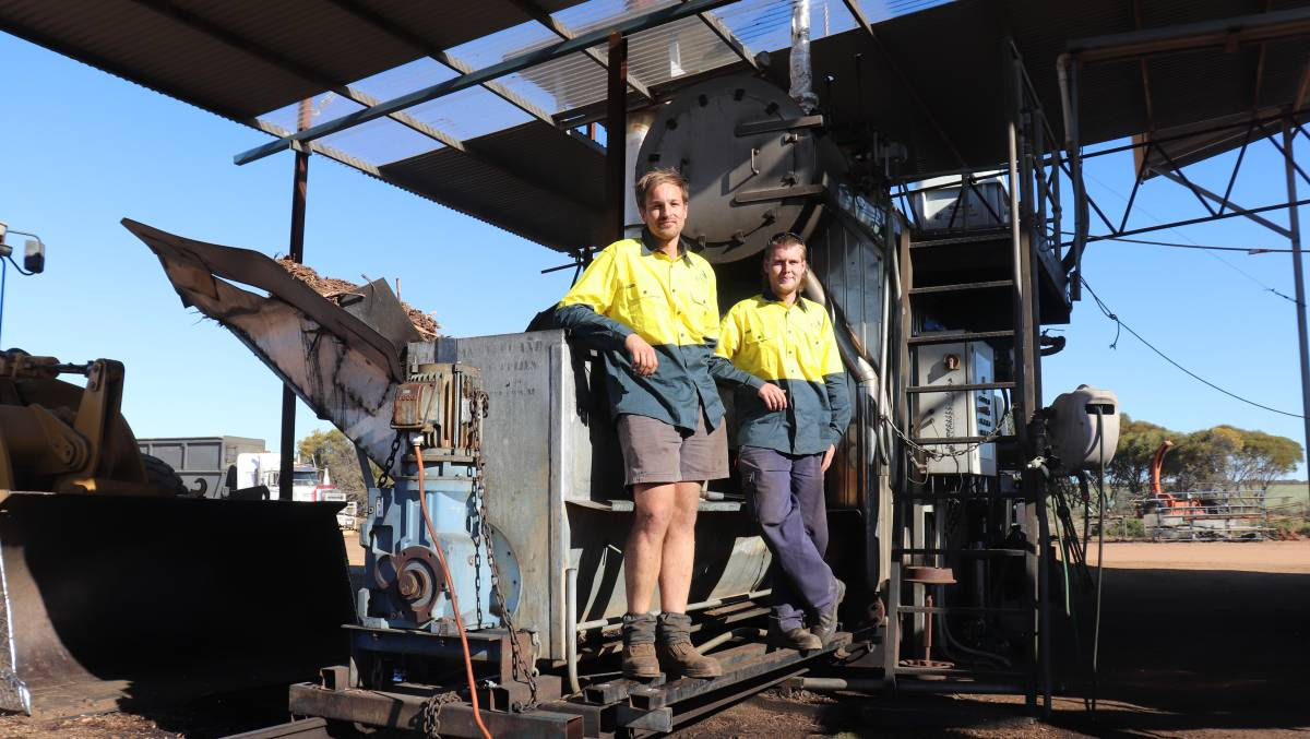 Jason Uyen (left) and Reece Ward at the hopper which feeds some of the spent dried biomass from previous distillations into a furnace that turns water in a tank above it into steam to be pumped through a shipping container packed with green eucalyptus biomass to extract the oil.