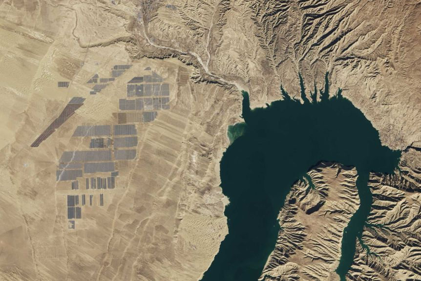 You view a satellite image of a large dam in the middle of light brown land with a large solar park visible to its left.