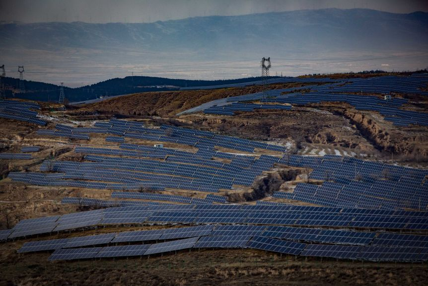 A birdseye view shows thousands of solar panels installed on hilly terrain in china