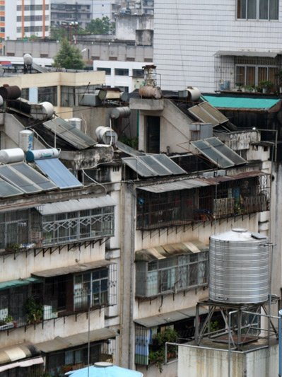 An an overcast day, you view tightly-packed medium-density apartment blocks stretching to the horizon with solar panels attached