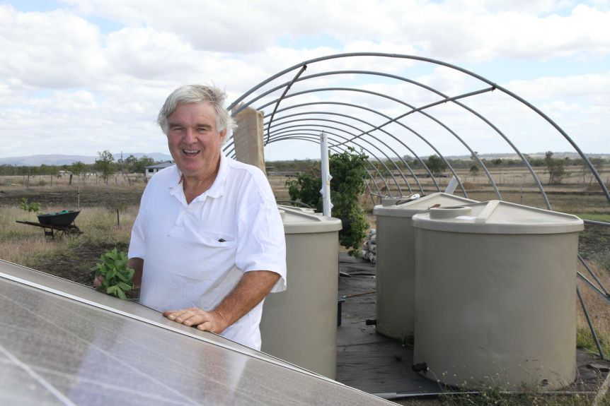 An older man with his hands on a solar panel, standing in front of an aquaponics set-up.