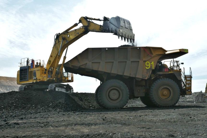 A truck is loaded with coal by a mine worker in a bob cat.